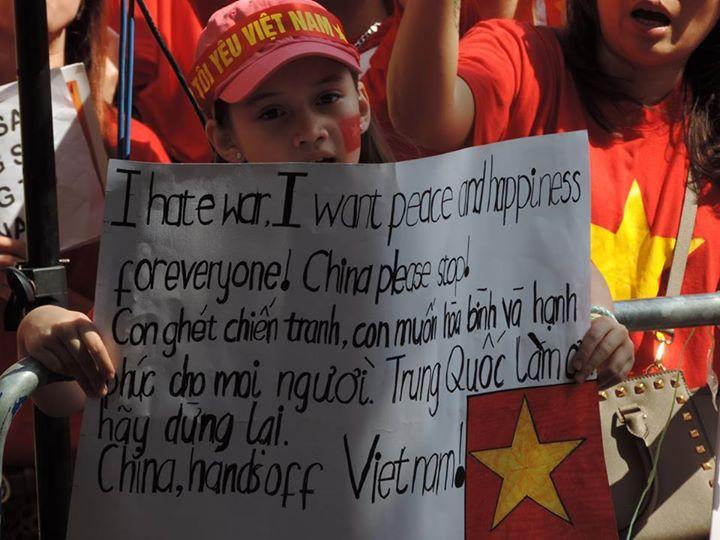 Một em bé mang hia dòng máu Anh - Việt mang biểu ngữ phản đối